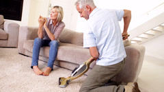 Man hoovering the carpet while partner relaxes Stock Footage