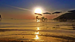 Beach sunset with silhouette of a woman using sun screen. Stock Footage