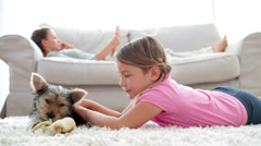 Little girl playing with puppy chewing bone with her mother reading on the sofa - stock footage