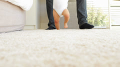 Father helping baby to walk across rug - stock footage