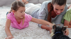 Cute siblings playing with puppy with their mother on the rug Stock Footage