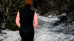 Woman hiking on a snowy mountain trail with a dog in late winter. - stock footage