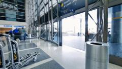 Airport workers moving stacks of luggage carts out terminal doors. Timelapse. - stock footage