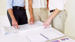 Team going over building plans with one woman smiling at camera - stock footage