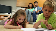 Siblings colouring on the floor while their parents are sitting on sofa Stock Footage