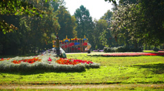 City park with green lawn and playground in the distance Stock Footage