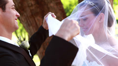Groom lifting his brides veil and kissing her - stock footage