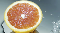 Halved grapefruit in running water Stock Footage
