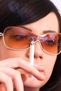 Health issues concept - Young girl smoking cigarette - stock photo