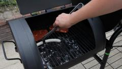 Fresh sausage and steak grilling outdoors on a barbecue grill. Stock Footage