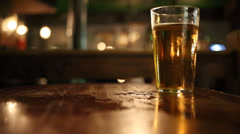 Pint glass of lager on pub table - stock footage