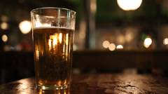 Pint glass of lager on pub table in English pub - stock footage