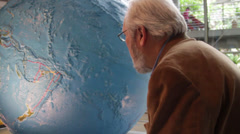 Asian old man rotating the globe Stock Footage
