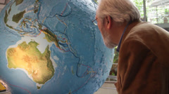 Old man in a museum lean in towrds globe - stock footage