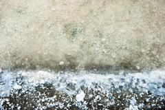 salt crystals in evaporation pond close up - stock photo