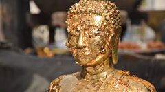 Buddha statue with gold leaves, close up Stock Footage