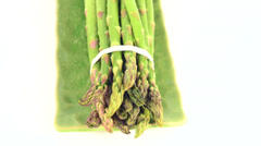 Asparagus being grabbed by hand and falling on plate Stock Footage