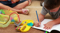 Young siblings doing arts and crafts on the rug Stock Footage