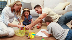 Young siblings doing arts and crafts on the rug with parents Stock Footage