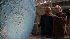 Two people exchange information while looking at the globe Stock Footage