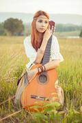 Hippie girl playing guitar on grass Stock Photos