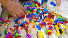 Child hand play with plastic toy blocks and having fun, joy Stock Footage