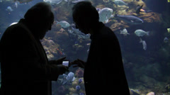 Two men in silouette at aquarium discussing about the phone Stock Footage