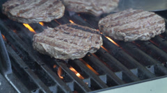 Burgers on BBQ being flipped Stock Footage