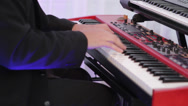 Stock Video Footage of masculine hands playing on a red synthesizer