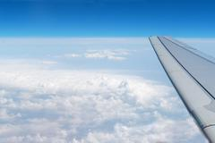 Airplane wings in the blue clouds Stock Photos