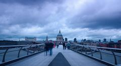 londoners walk over millenium bridge - stock photo