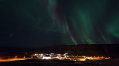 Aurora Borealis (Northern Lights) in Iceland with town Vik timelapse Stock Footage