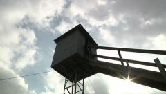 Stock Video Footage of Lookout Guard Tower Dark Clouds Timelapse Sunburst Prison Security Surveillance