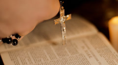 Man praying with rosary over open bible Stock Footage