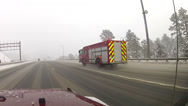 Stock Video Footage of Firetruck with lights on going down snowy highway