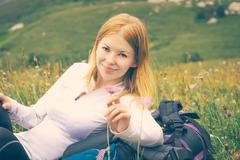 Woman traveler relaxing outdoor on green valley with flowers enjoying nature  Stock Photos