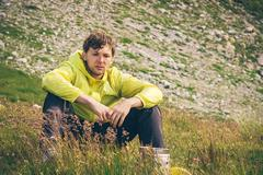 Man relaxing in mountains sitting on grass valley traveling hiking summer rec Stock Photos