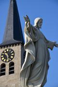 Patsas Jezus Kristuksen lähellä kellotorni kirkko Kuvituskuvat