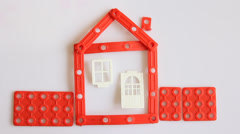 Human hands build red house on white background. - stock footage