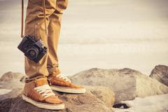 Feet man and vintage retro photo camera outdoor travel lifestyle vacations co Stock Photos