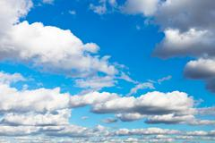 White woolpack clouds in blue sky Stock Photos