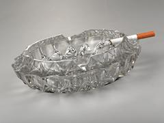 old cigarette ashtray in glass with a cigarrette burning - stock photo