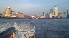 High speed boat with Canary Wharf towers in sunlit backdrop Stock Footage