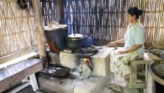 A lady heats the beans to make kopi luwak Stock Footage
