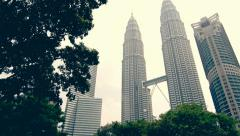 An epic tilt of the PETRONAS towers that includes the track and clock tower Stock Footage