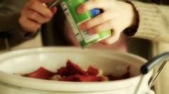Woman putting tomato paste into crockpot Stock Footage
