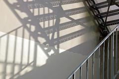 Metallic staircase, game of shade and light - stock photo