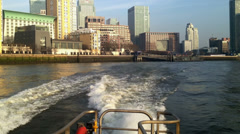 Onboard high speed boat with view of sunlit Canary Wharf London - stock footage