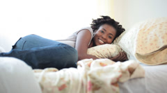 Black woman laying on bed on top of fluffy comforters Stock Footage