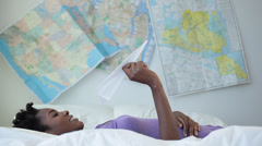 Black woman laying on bed playing with a paper airplane with maps on the wall Stock Footage